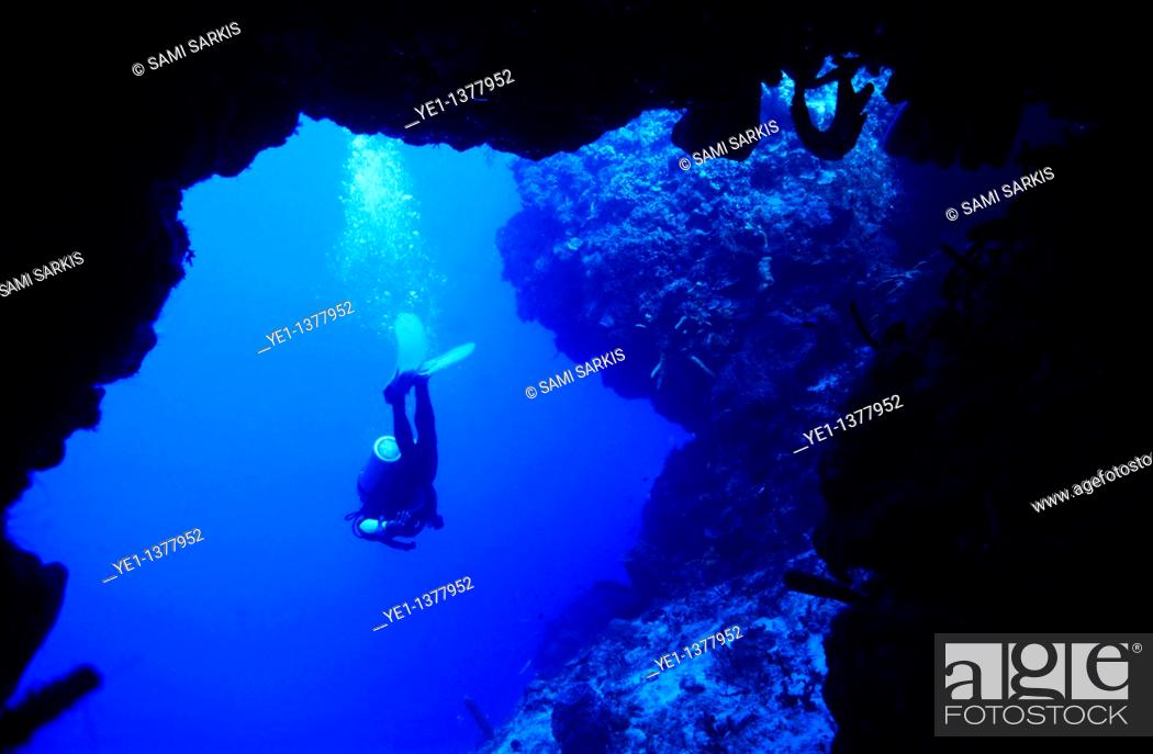 Stock Photo: Diver swimming out of a cave.
