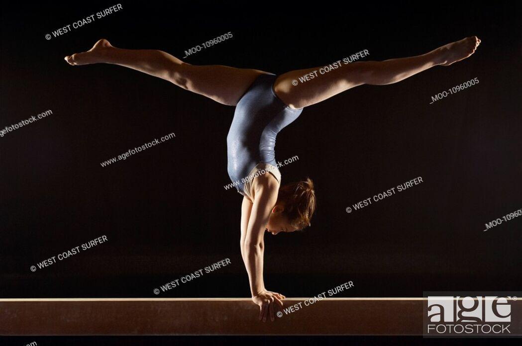 Stock Photo: Gymnast 13-15 doing split handstand on balance beam side view.