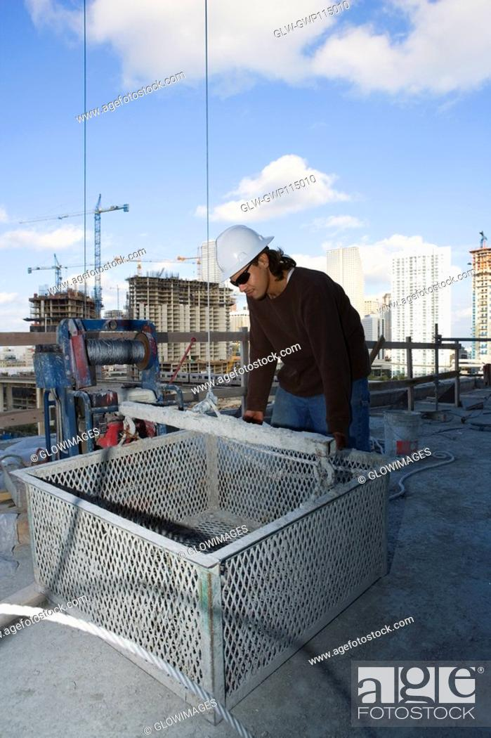 Stock Photo: Male construction worker leaning against a basket at a construction site.