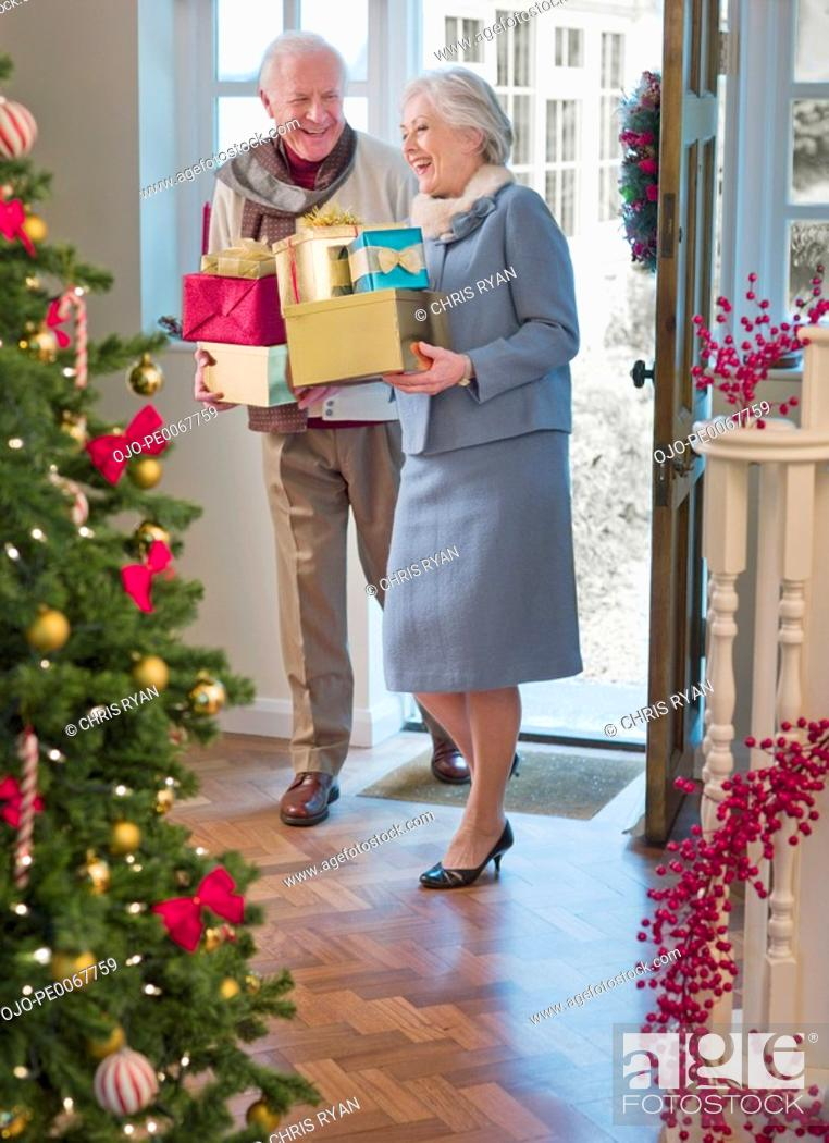 Stock Photo: Couple entering house with Christmas gifts.