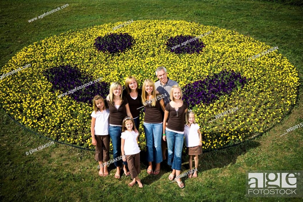 Stock Photo: Large family group on hill with happy face floral display.