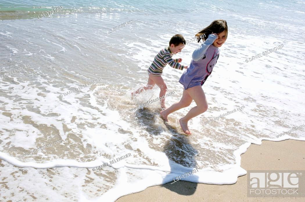 Stock Photo: Boy and girl playing in the beach hand in hand, El Saler beach, Albufera de Valencia Nature reserve, Valencia, Spain.