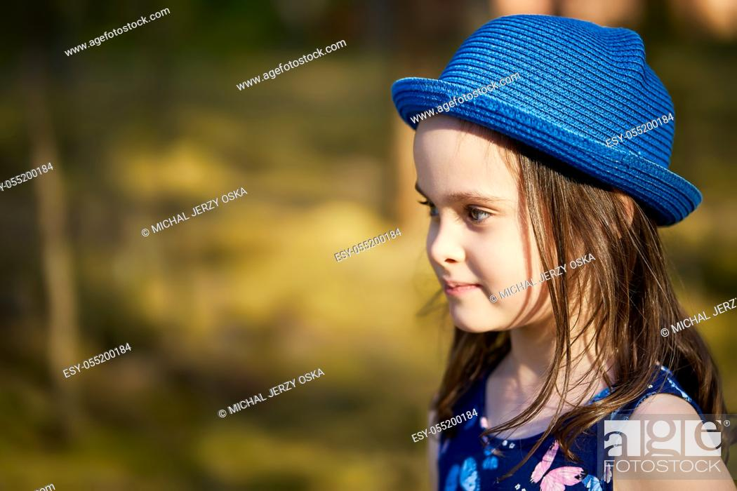Photo de stock: adorable little girl in a blue hat posing in the spring pine forest.