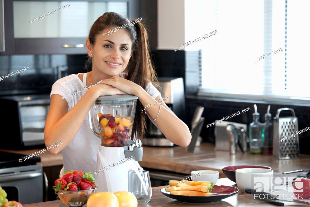 Stock Photo: Woman leaning on blender full of fruit.
