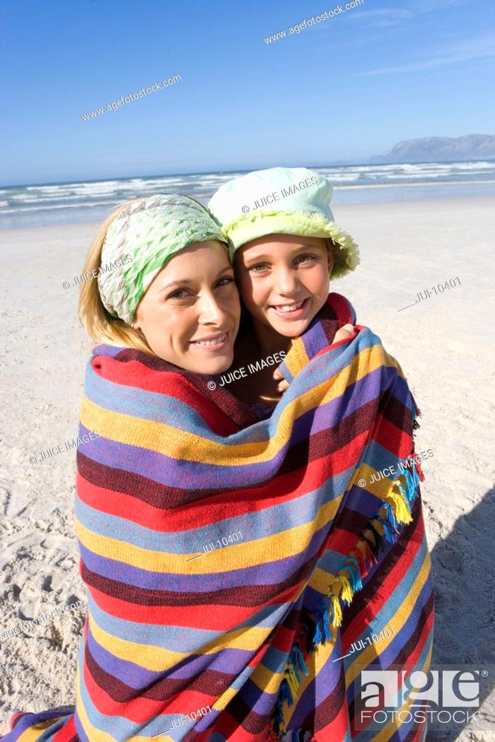Stock Photo: Mother and daughter 5-7 wrapped in blanket on beach, smiling, portrait, close-up.