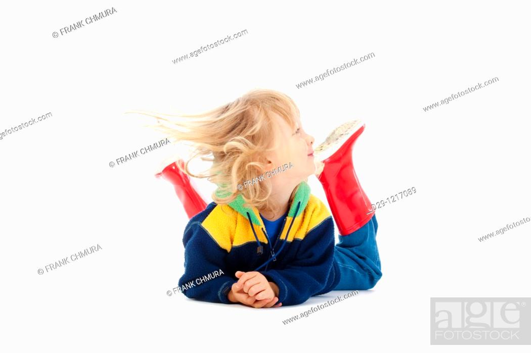 Stock Photo: boy with long blond hair lying on the floor - isolated on white.