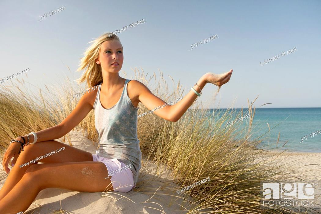 Imagen: Healthy young woman sitting in the dunes letting sand flow through her fingers.