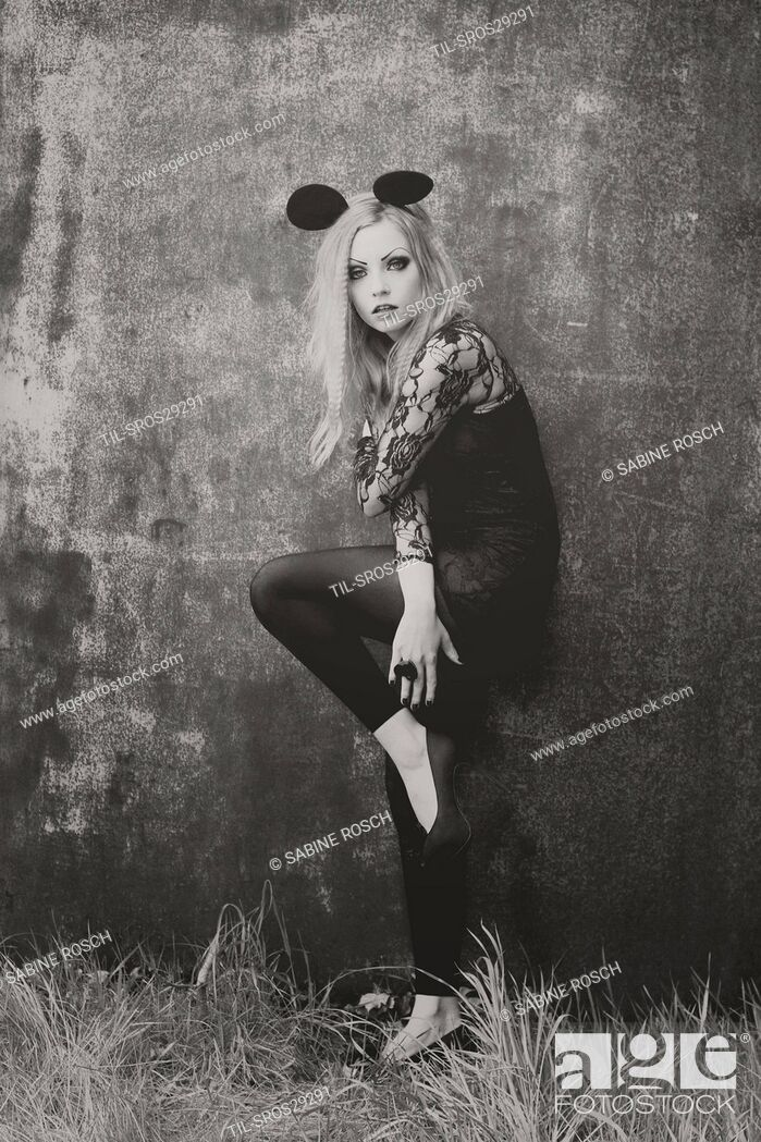 Imagen: black-white photo of young woman with blonde hair wearing a black lace dress and wearing mouse ears wearing a heart ring.