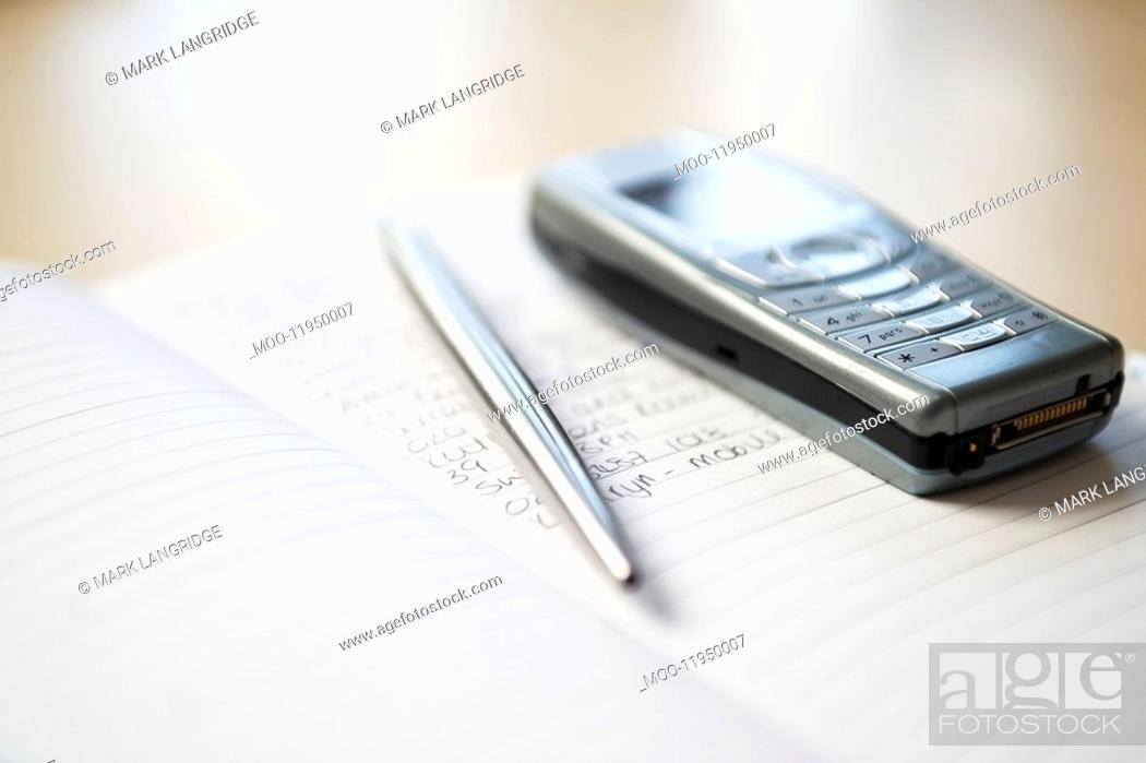 Stock Photo: Still life of mobile phone and silver pen resting on notebook.