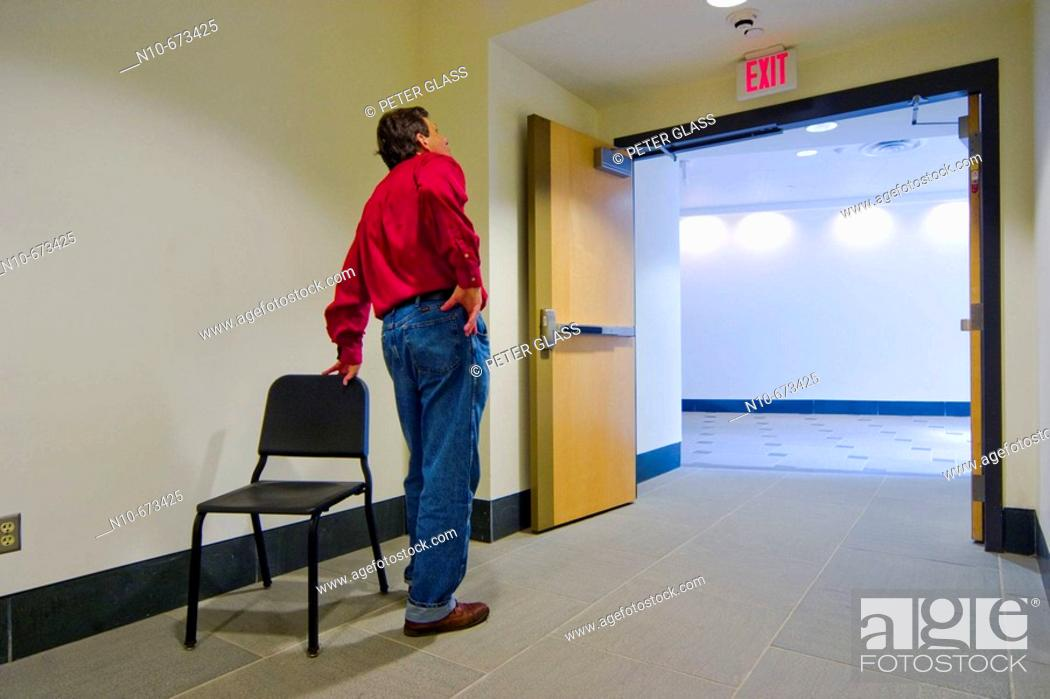 Stock Photo: Man, wearing a red shirt, standing next to an empty chair that is near open doors in a college building.