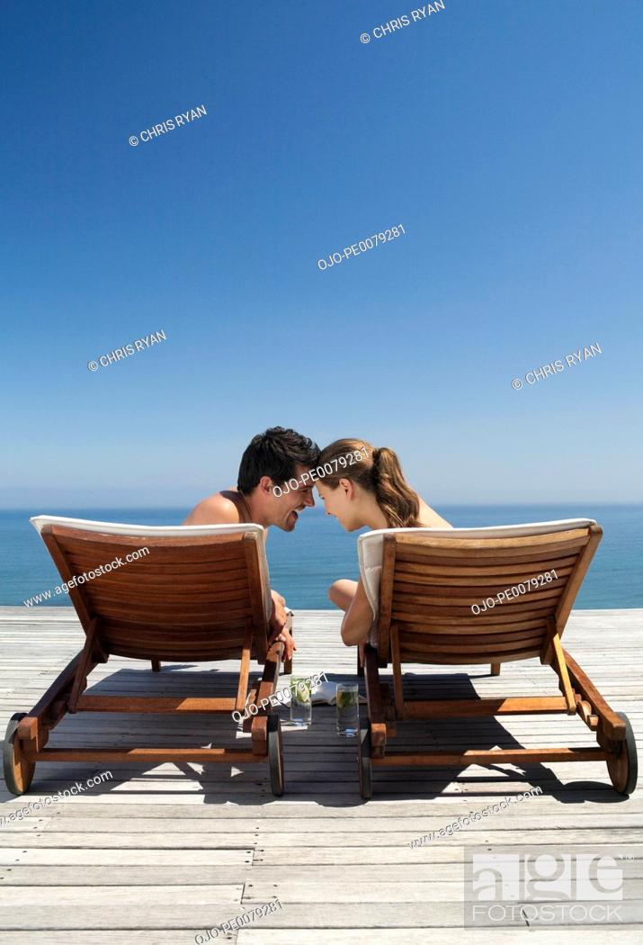 Stock Photo: Couple sitting in lounge chairs near ocean.