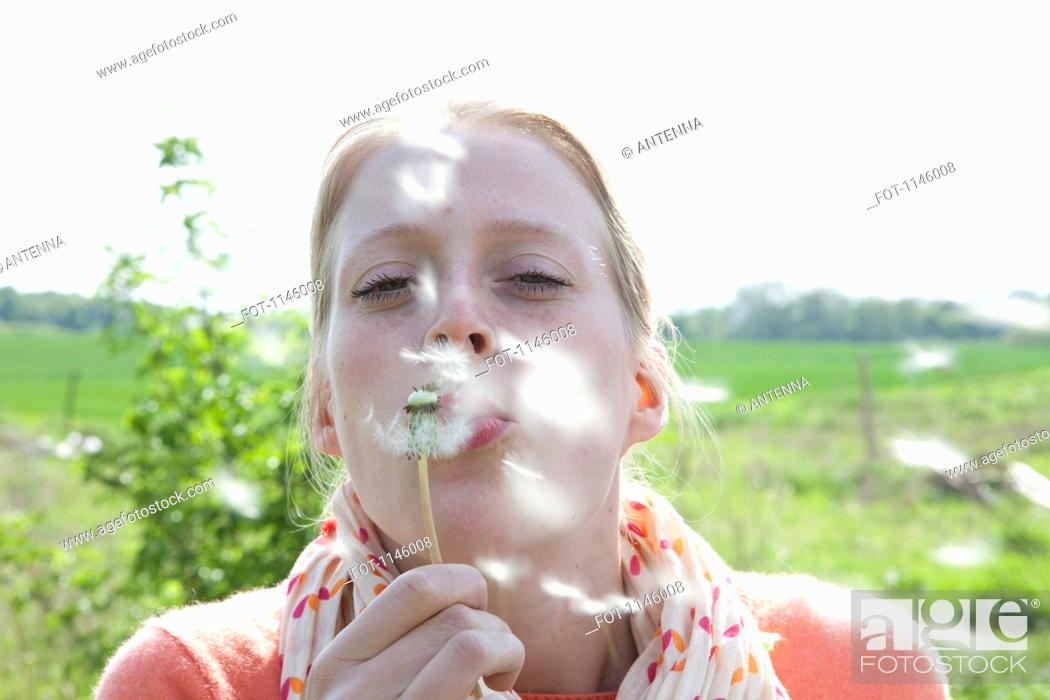 Stock Photo: A woman blowing on a dandelion, close-up.
