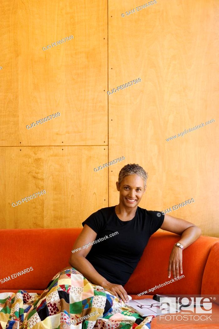 Stock Photo: Woman sitting on sofa with magazine in modern home.