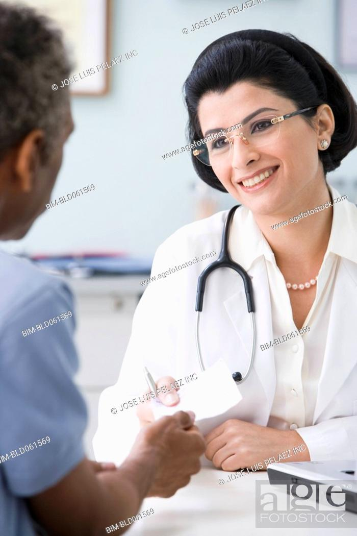 Stock Photo: Middle Eastern female doctor handing prescription to patient.