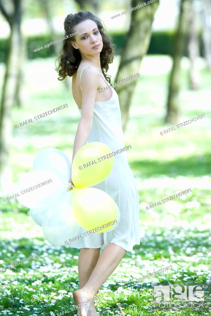 Stock Photo: Young woman walking in meadow, holding balloons, looking over shoulder at camera.