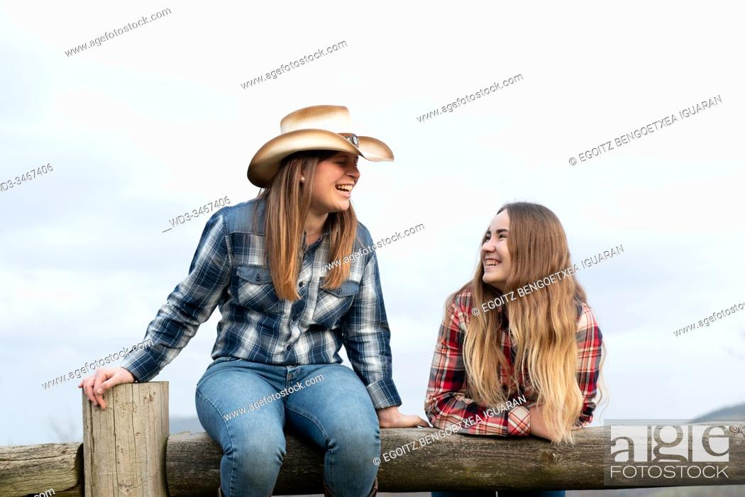 Imagen: Young and teenager blonde cowgirls laughing on a wooden barrier.