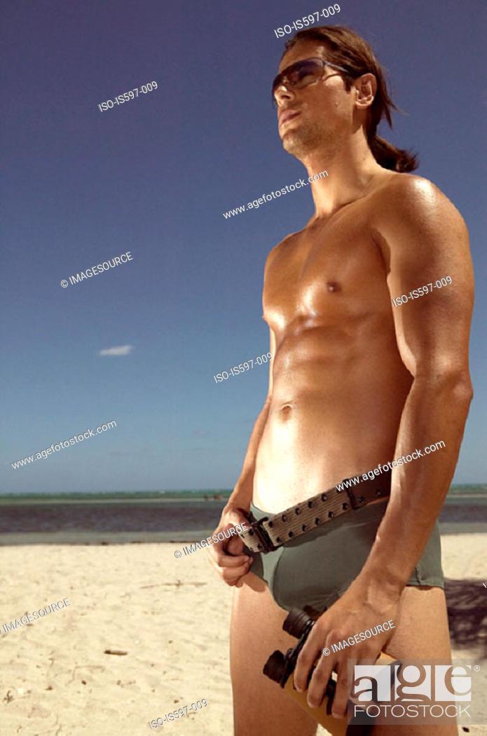 Stock Photo: Man with binoculars on beach.