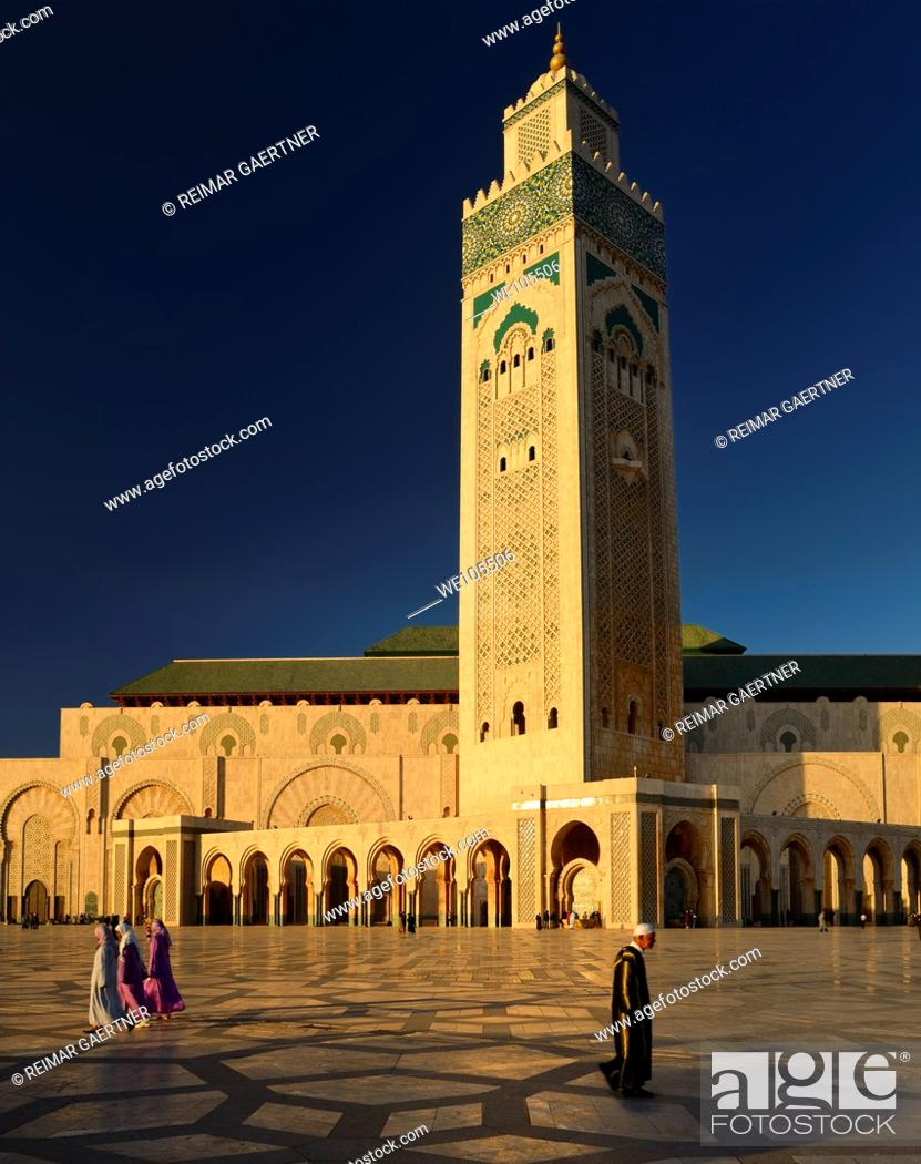 Stock Photo: Moroccan man and women walking on the plaza of the Hassan II Mosque Casablanca at sunset, Morocco.