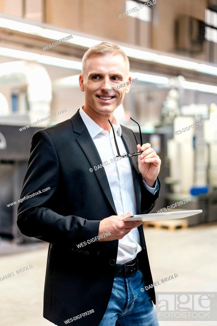 Stock Photo: Smiling businessman holding glasses and tablet in a factory.