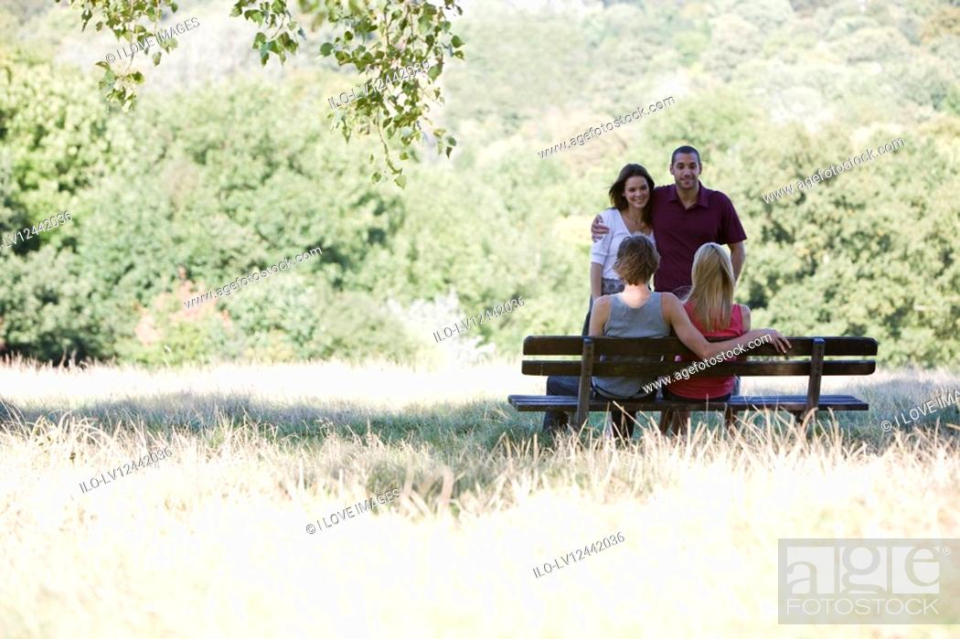 Stock Photo: Two young couples talking by a bench in a park.