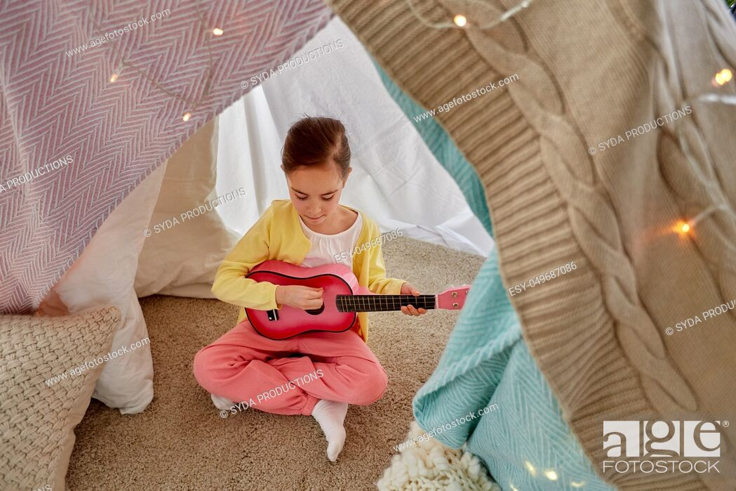 Stock Photo: little girl playing guitar in kids tent at home.