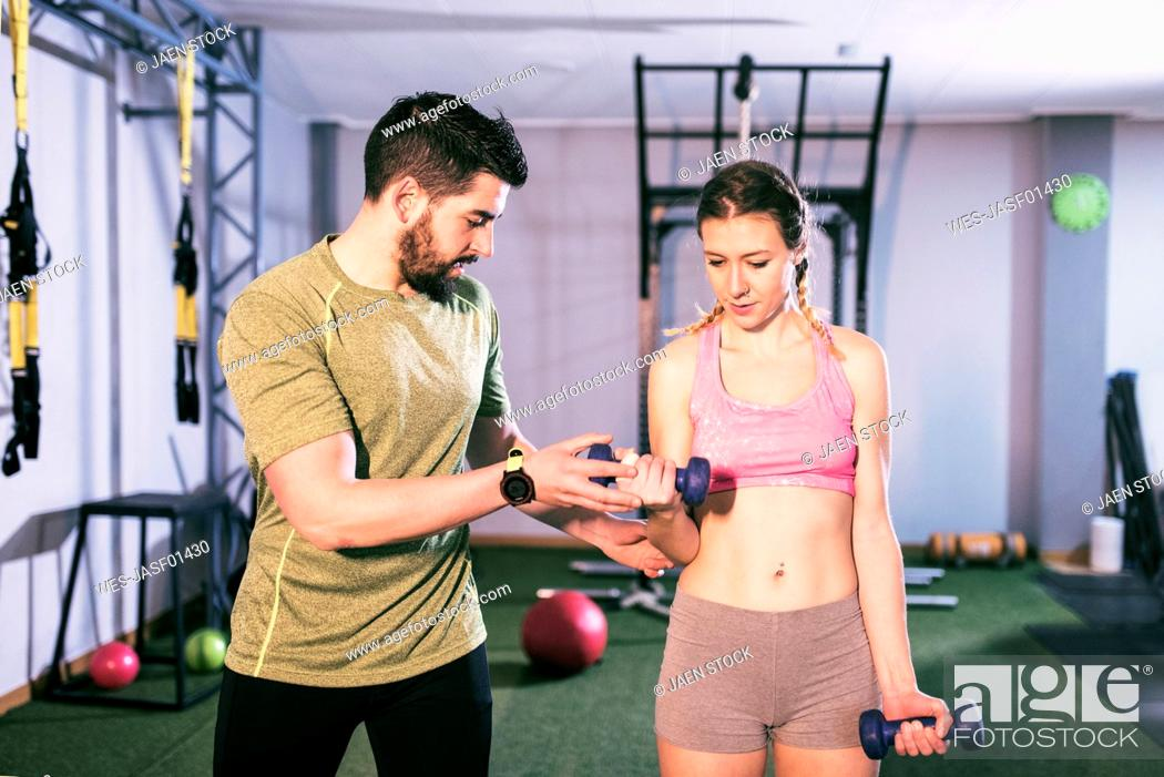 Stock Photo: Man training woman lifting weights in gym.