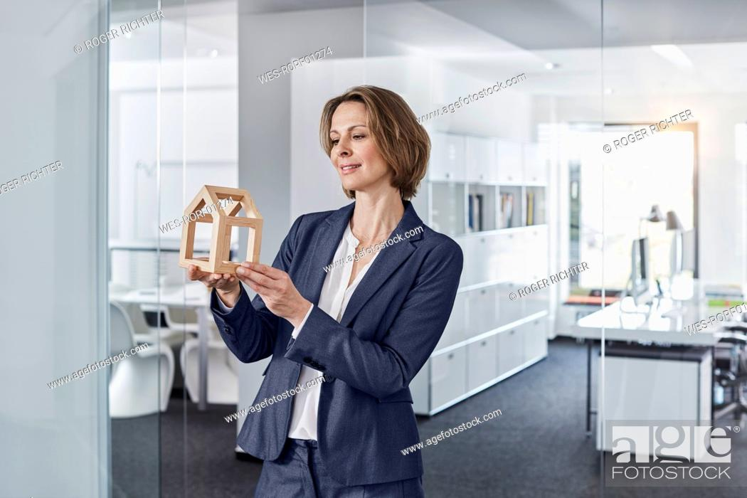 Stock Photo: Smiling businesswoman looking at architectural model in office.