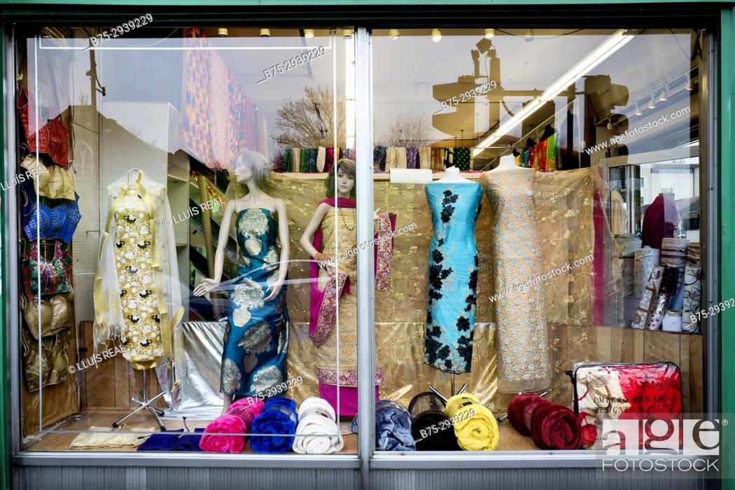 Stock Photo: Indian fashion store. Shop window with female mannequins in Indian clothes. Glass reflections. London, England.