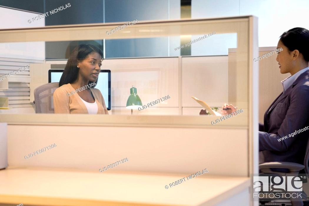 Stock Photo: Businesswomen having meeting in office cubicle.