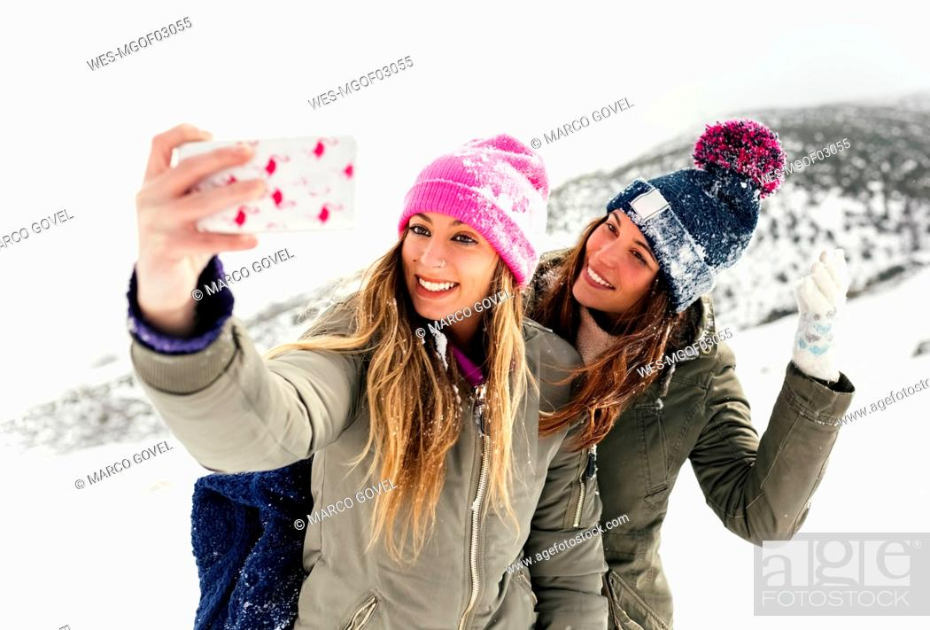 Stock Photo: Two friends taking smart phone selfies in the snow.