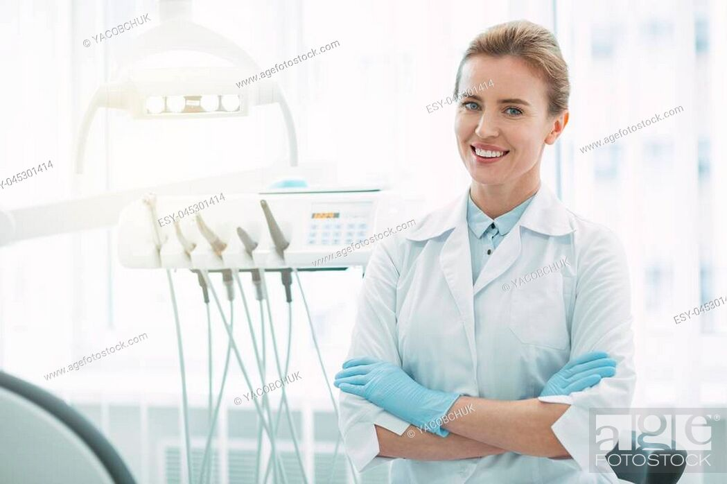 Stock Photo: Feeling inspired. Joyful female dentist smiling and standing with her arms crossed.