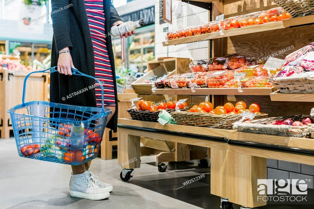 Stock Photo: Low section of woman holding basket while shopping in supermarket.