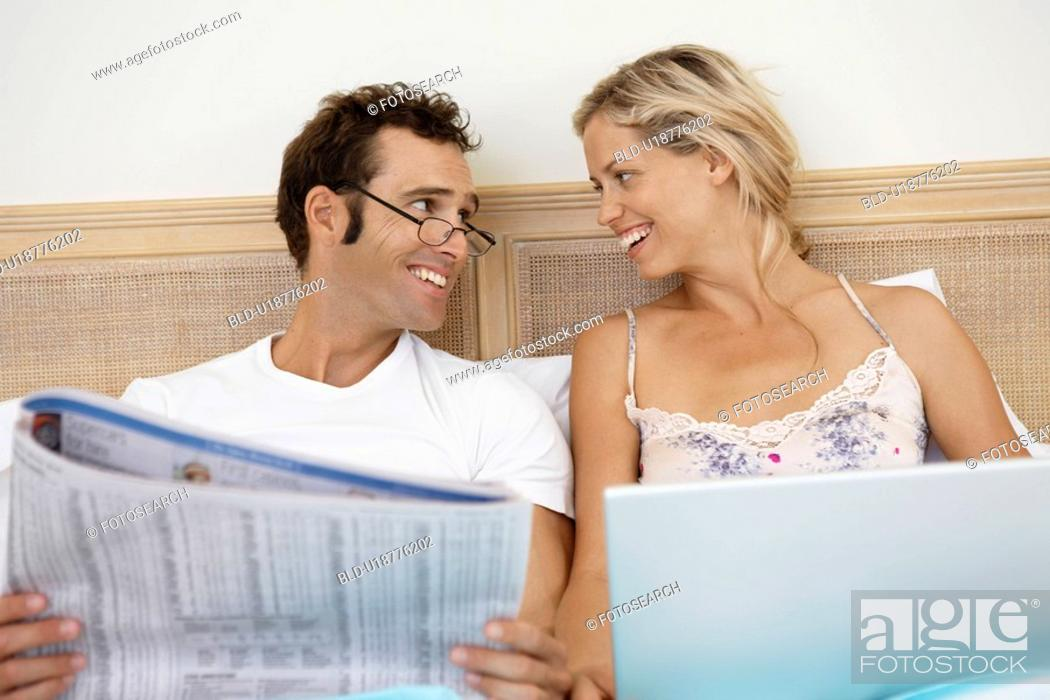 Stock Photo: Mid adult couple using laptop and reading newspaper in bed.