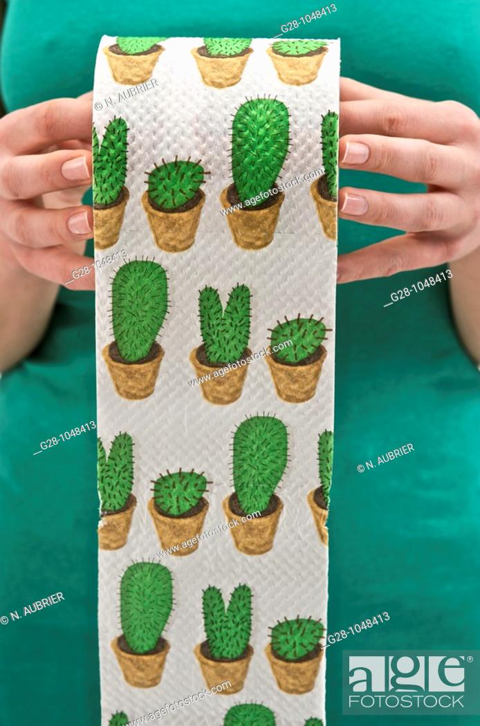Stock Photo: woman's hands holding a roll of toilet paper printed with green cactuses to express toilet difficulties.