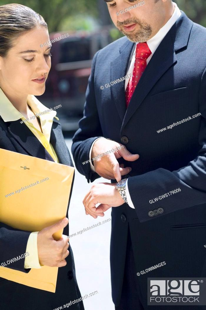 Stock Photo: Businessman and a businesswoman checking the time in a wristwatch.