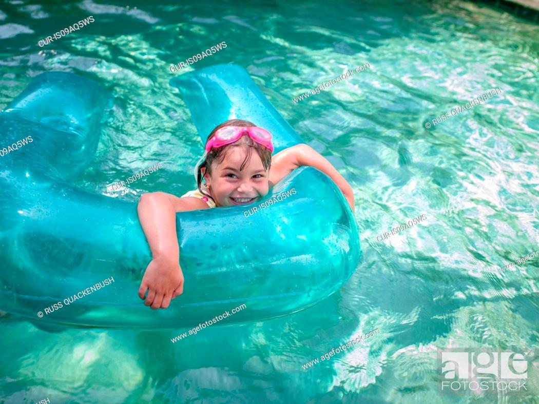Imagen: Portrait of girl playing with inflatable ring in garden swimming pool.