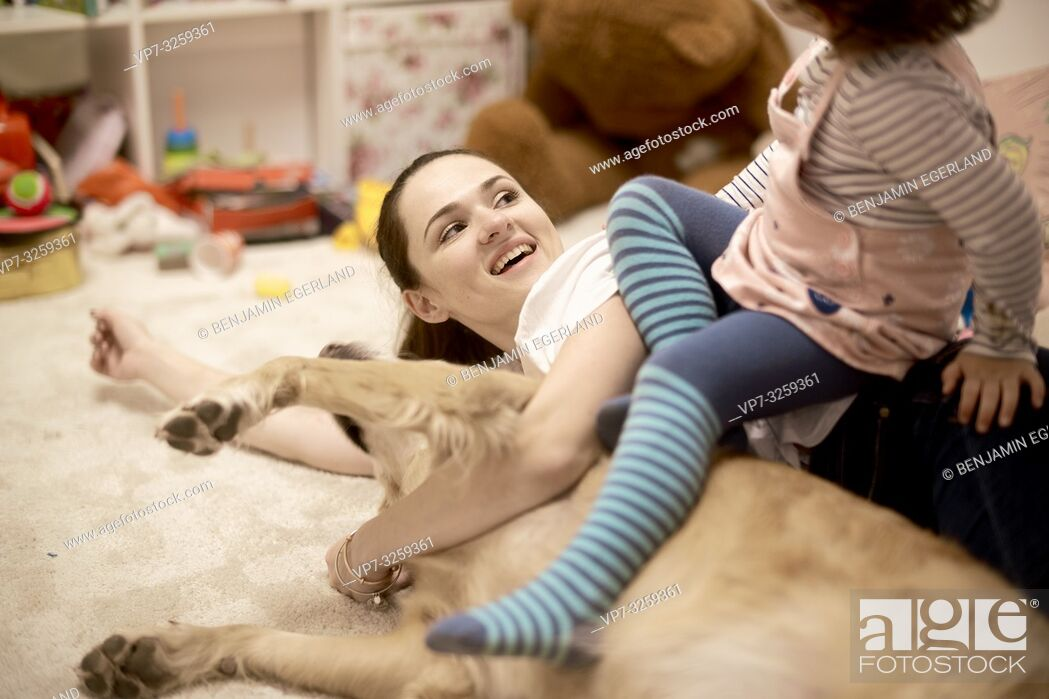 Stock Photo: mother with toddler and dog lying on the floor in child's room, in Munich, Germany.