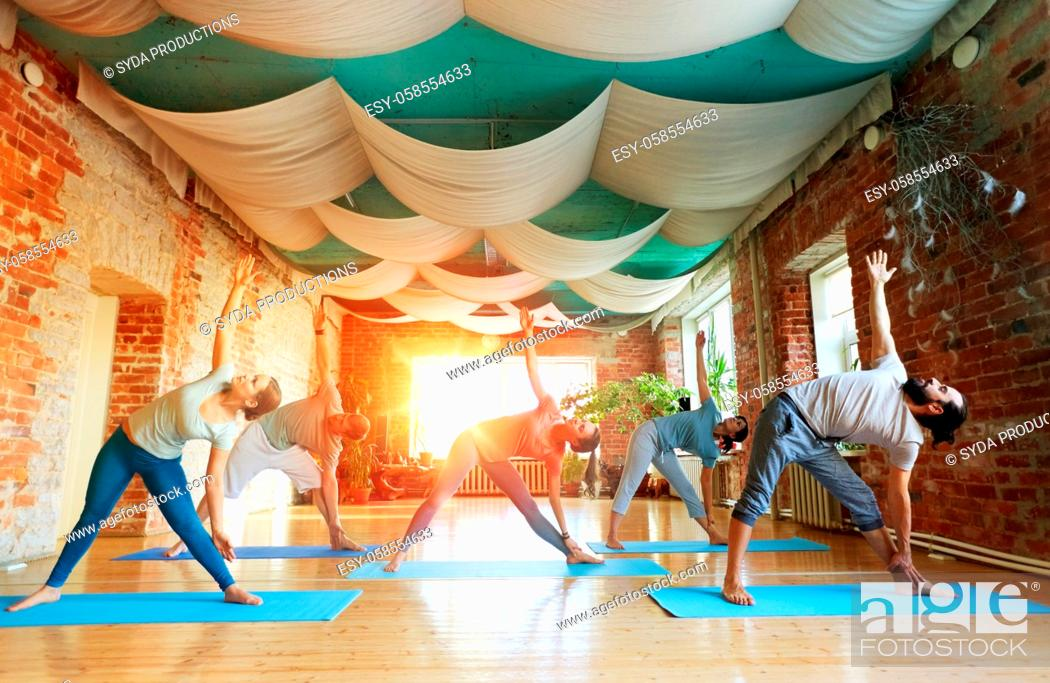 Stock Photo: group of people doing yoga triangle pose at studio.
