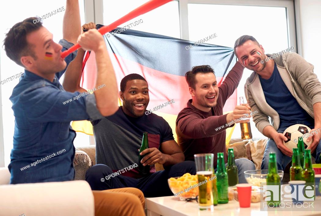 Photo de stock: Group of men watching sporting event on television holding German flag and football, celebrating.