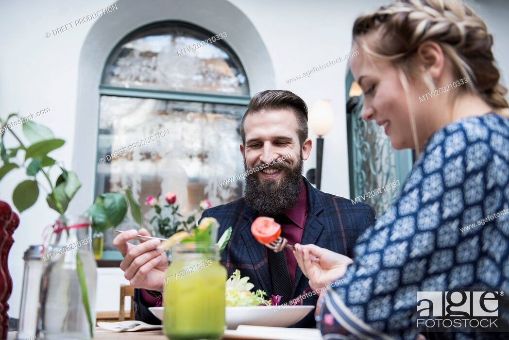 Stock Photo: Young couple eating salad at restaurant.