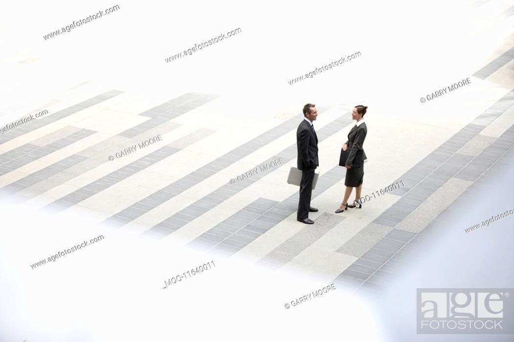 Stock Photo: Businessman and businesswoman standing and talking in outdoor plaza elevated view.
