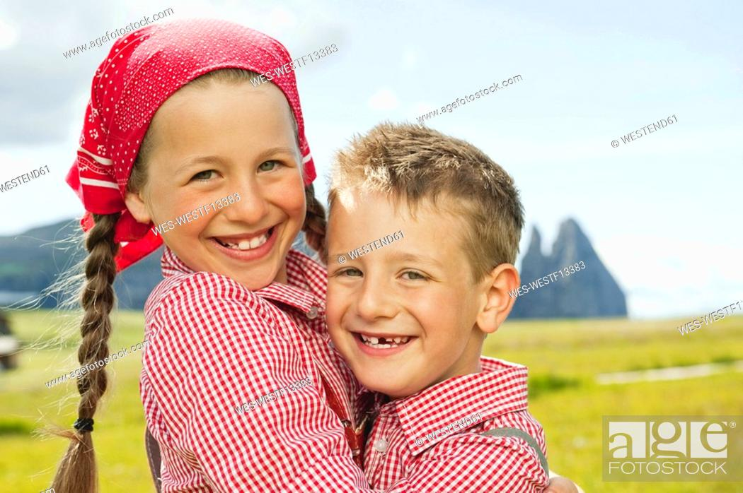 Stock Photo: Italy, Seiseralm, Boy 6-7 and girl 8-9 in field, embracing, smiling, portrait, close-up.