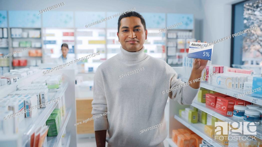 Stock Photo: Customer holding a box of vitamins.