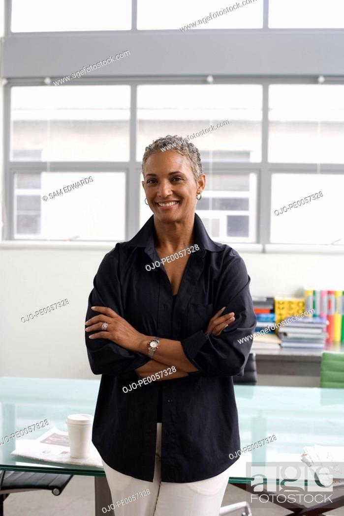 Stock Photo: Businesswoman standing in office smiling.
