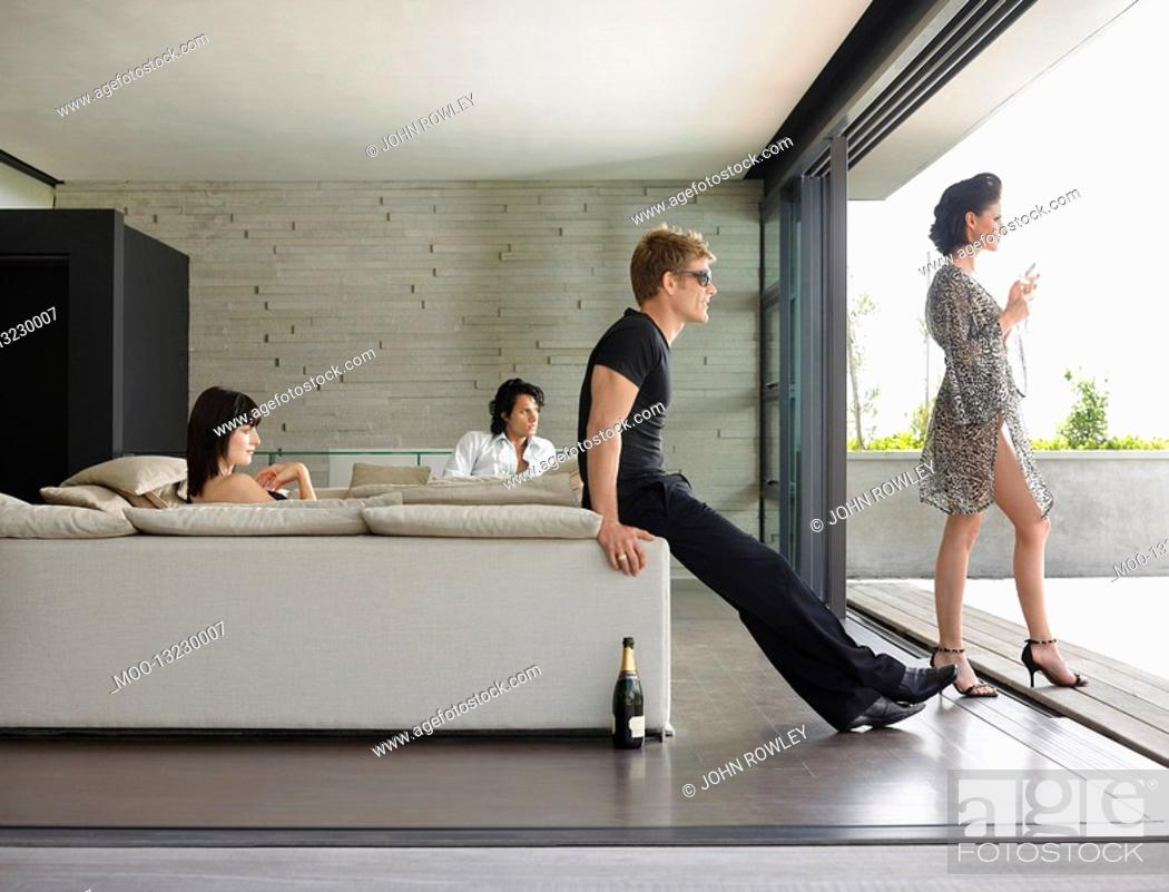 Stock Photo: Young people drinking champagne in living room.