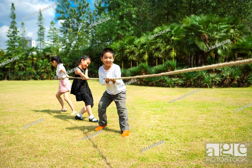 Stock Photo: Children standing in a row and playing tug-of-war together.