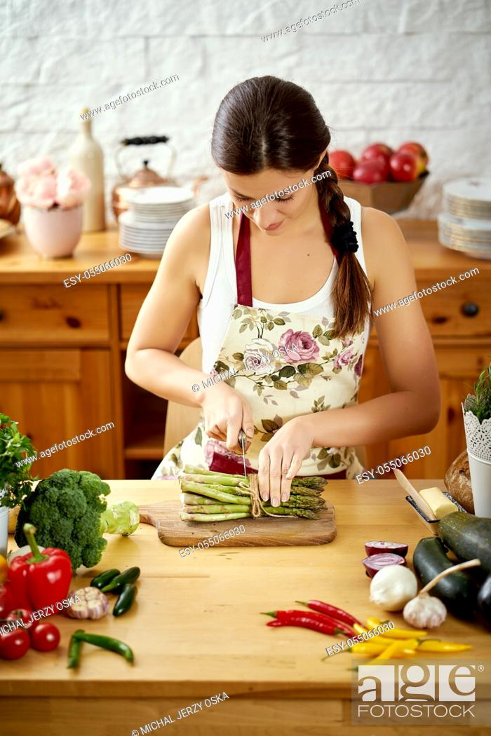 Stock Photo: beautiful young woman, brunette slicing asparagus in the kitchen at a table full of organic vegetables.