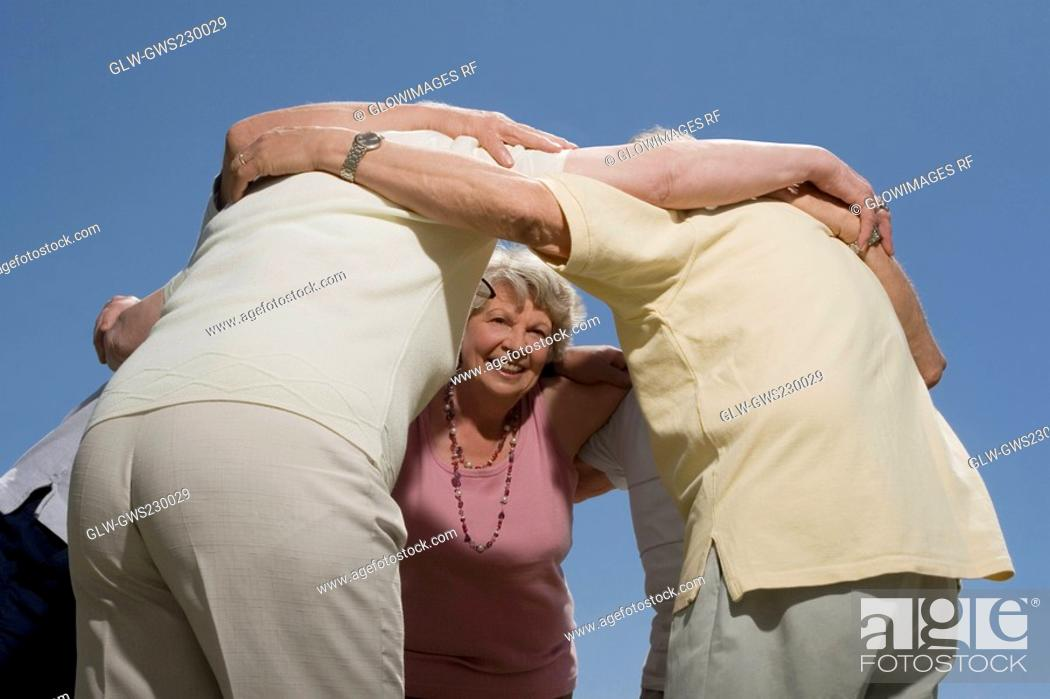 Stock Photo: Low angle view of senior people standing in a huddle.