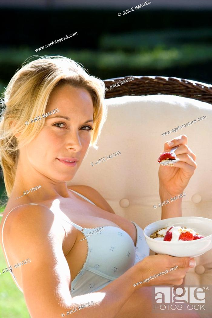Stock Photo: Young woman eating breakfast in underwear outdoors, portrait, close-up.
