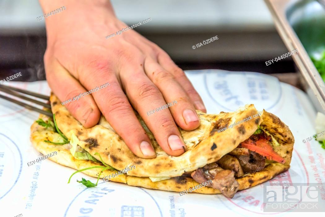 Imagen: Man hand preparing grilled delicious liver Turkish shish kebab over lavash to serve.